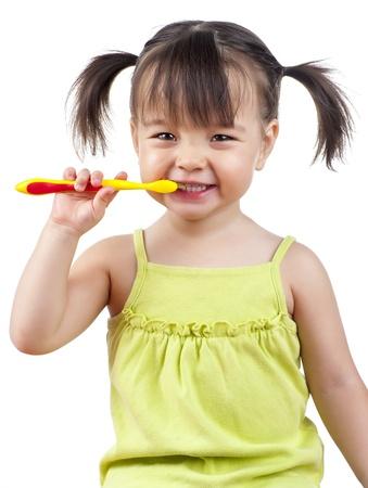 白で隔離される彼女の歯をブラッシングしながら笑顔の幼児 写真素材