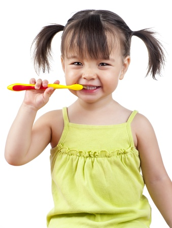 Toddler smiling while brushing her teeth isolated on white Stock Photo