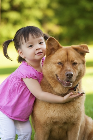 Girl and dog together outside photo