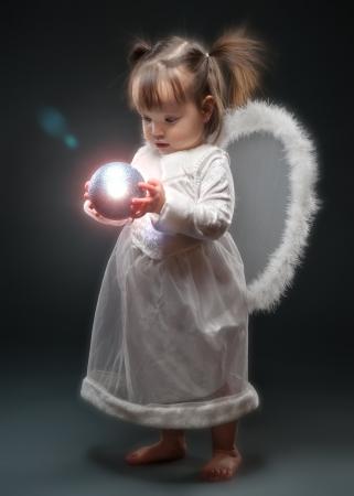 Kleines Mädchen als Engel Holding Weihnachtszierde gekleidet