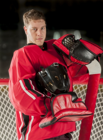 Goalie portrait posing with his gear and helmet off photo