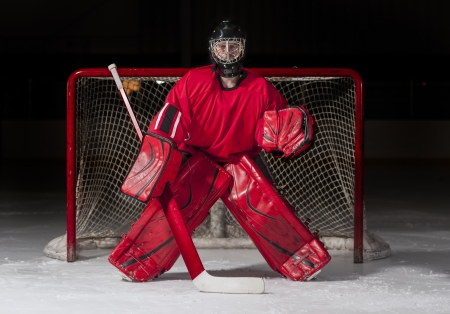 goal keeper: Ice hockey goalie in front of a goal net