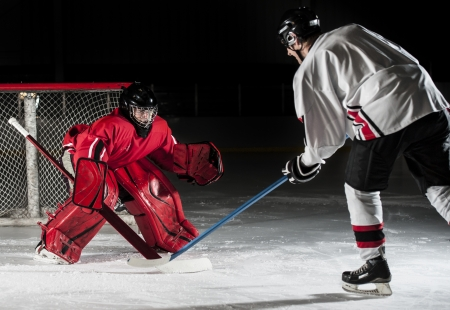 hockey sobre hielo: Ice hockey acción tomada con reproductor hacia adelante y portero