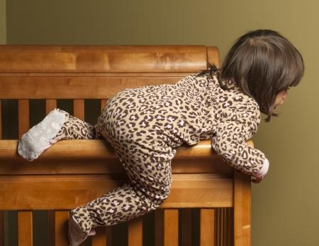 niño escalando: Niño saliendo de su cuna. Foto de archivo