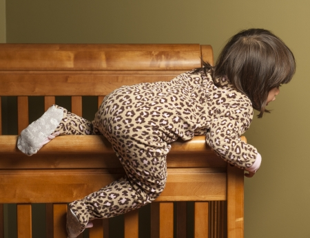baby crib: Toddler climbing out of her crib.