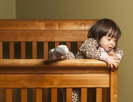 유아는 그녀의 침대의 등반. 스톡 콘텐츠