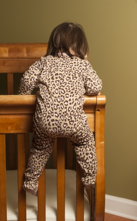 naptime: Toddler climbing out of her crib.