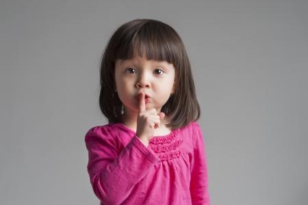 guardar silencio: Niña haciendo un gesto guardar silencio