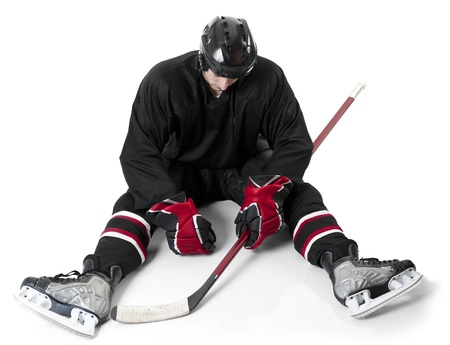 Ice hockey player sitting on ice with disappointment photo