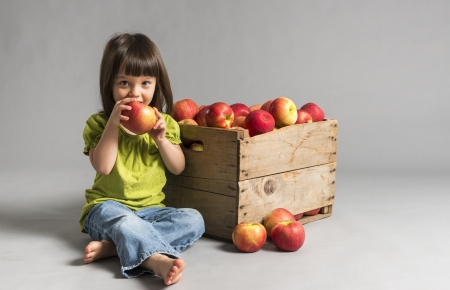 three year old: Little sitting girl eating apple with crate of apples beside her
