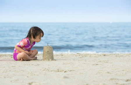 Little girl blowing on cake made with sand. Photo taken near the ocean. photo