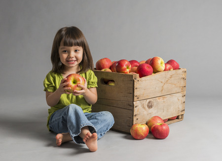 Child with crate of apples beside her. photo