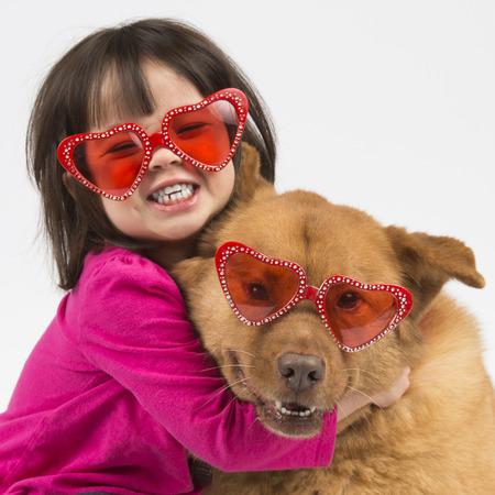 아이는 개에 포옹을주는. 두 심장 모양의 선글라스를 착용합니다.