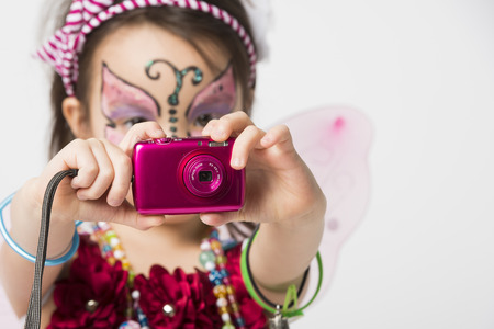 Little girl with face painting holding  a snapshot camera photo