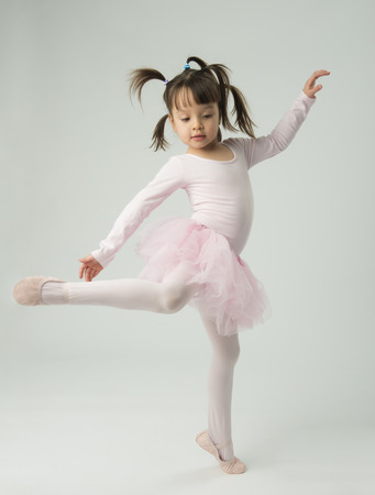 asian toddler: preschool age girl dancing and wearing a ballet tutu