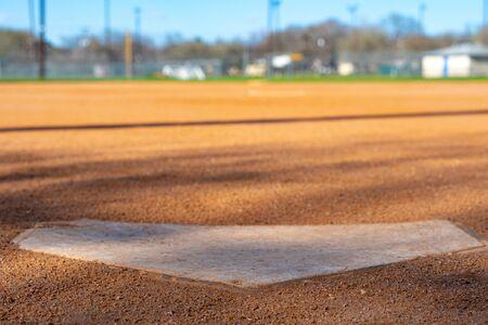 Niedrige Winkelnahaufnahme der Home-Plate mit Blick auf das Außenfeld auf einem Baseball-Diamanten der Jugendliga.