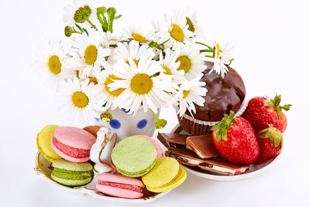 camomiles: Camomiles in vase, macaroons on saucer with strawberry and chocolate