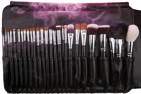 Makeup brushes set in leather case. Pink smoke. Isolated. White background. Stock Photo