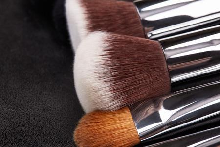 leatherette: Makeup brushes set on black leather background.