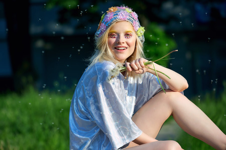 Young blond girl in sparkling hat with dandelions. Stock Photo