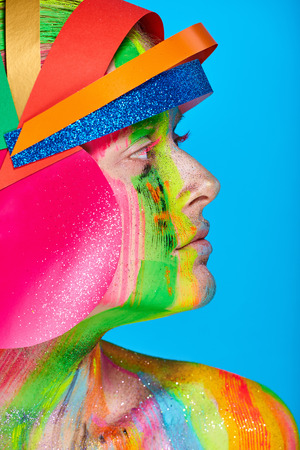 Model with colorful abstract makeup in multicolored helmet on blue background. Stock Photo