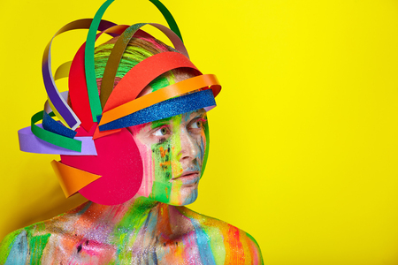 Model with colorful abstract makeup in multicolored helmet on yellow background.