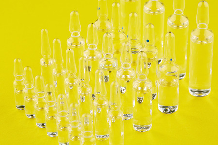 Ampoules with medicine on yellow background.