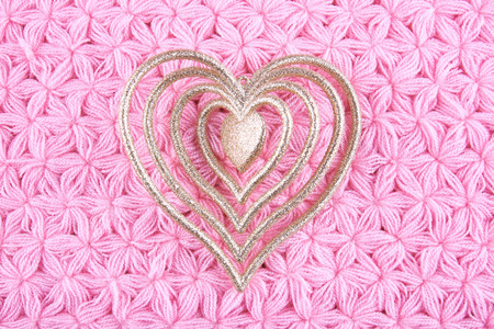 Heart shaped Christmas tree decorations on pink knitted napkin.