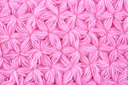 Pink woolen texture background. Macro of knitted cloth.