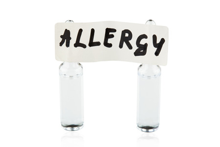 Tablet with written word ALLERGY stuck on two ampoules. Isolated.