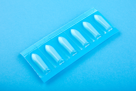 Plastic package with suppository on blue background.