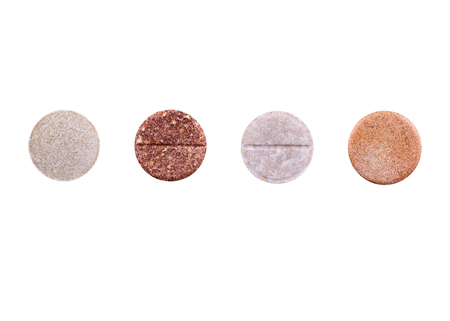 Four brown pills isolated on white background. Medicine.