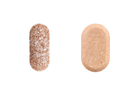 Two brown oval pills isolated on white background.