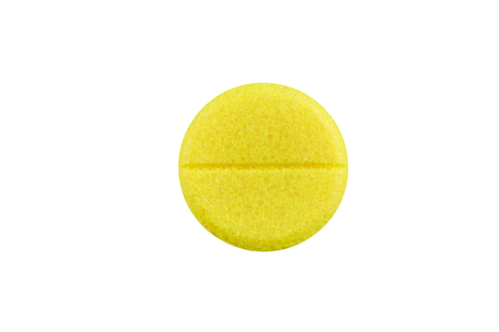 Macro photo of yellow pill. Isolated on white background.