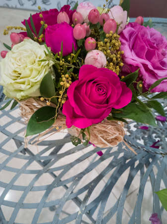 On the original table is a bouquet of ts charming roses of three flowers. Pink, white and red. Green twigs and yellow decorations are added to the bouquet