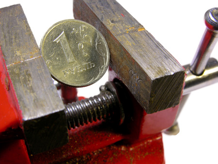 frugality: A cut one rubles half-coin squeezed in a metal vise jaws, concept of financial crisis and currency devaluation in Russian Federation. Stock Photo