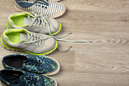 Various pairs of colorful sneakers laid on the wooden floor background