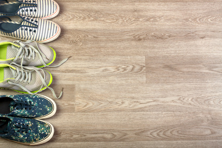 Various pairs of colorful sneakers laid on the wooden floor background. Background for a site about sports.