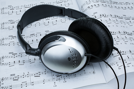 Silver headphones and piano sheet music as background Reklamní fotografie