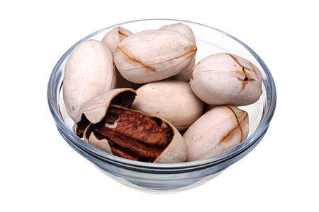 pekan: Pecan nuts in glass cup on white background with clipping path Stock Photo