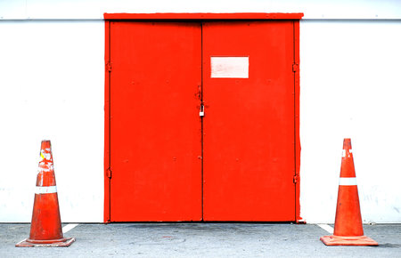 red door: Red door with warehouse closeup and road cones