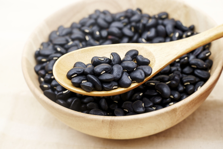 Wooden bowl full of dry black beans