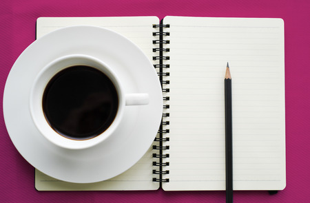 Coffee in white cup with Journal book and pencil