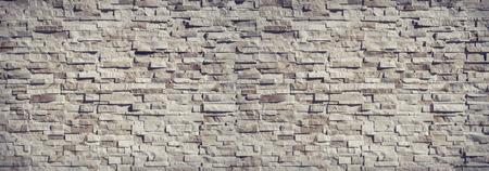De muurachtergrond van de aardsteen en textuurfoto Stockfoto