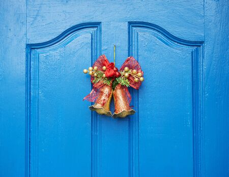Christmas red bow  hanging on old wooden blue door