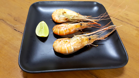 Grilled shrimp on a black plate on a wooden table with lemons. Stock Photo