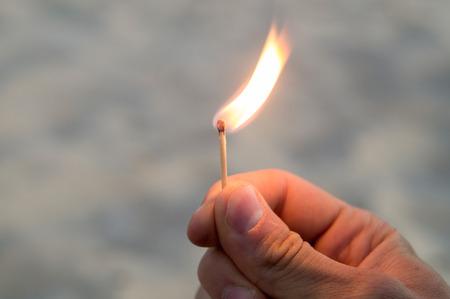 Mão direita do homem adulto que guarda um fósforo por dois dedos, com fundo da areia. A chama da partida apontando para a direita e para cima.