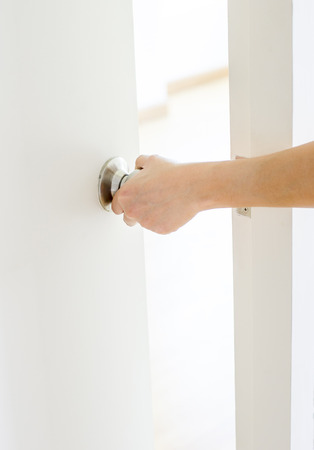 closed door: Hand opening door knob-white door Stock Photo
