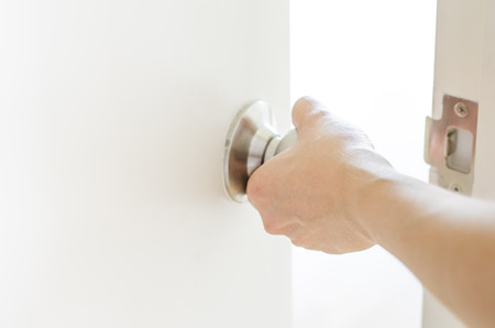Hand opening door knob-white door Stock Photo