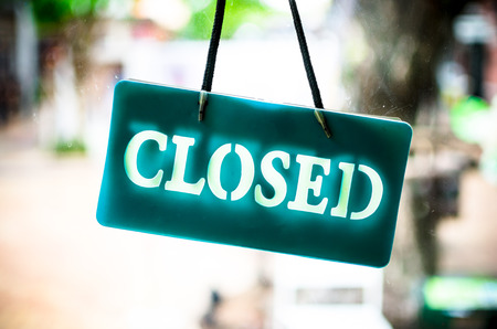 closed: Close sign hanging on glass of shop.